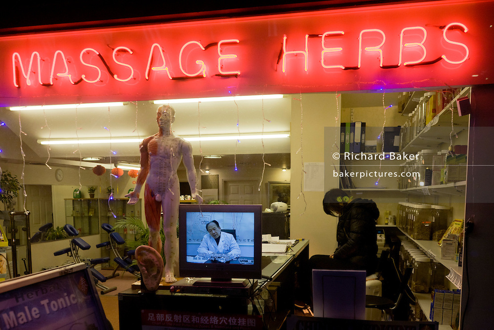 Tired assistant with Doctor on TV screen at a traditional Chinese herbalist's shop window in London's West End.