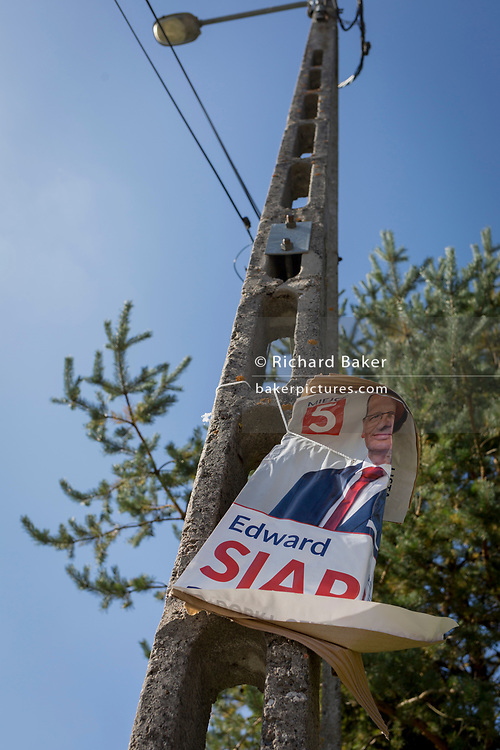 """A torn election poster for a Polish political candidate, on 21st September 2019, in Jaworki, near Szczawnica, Malopolska, Poland. Poland's parliamentary elections will be held on 13 October 2019 when all 460 members of the Sejm and 100 senators will be elected. The Sejm of the Republic of Poland is the lower house of the Polish parliament. It consists of 460 deputies elected by universal ballot and is presided over by a speaker called the """"Marshal of the Sejm of the Republic of Poland"""""""