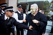 "Julian Assange at the Occupy London demonstration 15th October 2011. Seen here after arriving in a taxi with his own security, he tries to get through police lines wearing a black cape, hood and mask. He was immediately asked to take off the mask where upon he was dragged through the lines by the police, mask removed and questioned for a few minutes. He was then given a caution and released. According to the people he was with, he was just there to support the demonstration, but as usual, caused some publicity. Julian Assange is the Australian publisher and Internet activist. Editor in chief of WikiLeaks, the whistleblowing website and conduit for worldwide news leaks. Protests spread from the US with this demonstrations in London and other cities worldwide. The 'Occupy' movement is spreading via social media. After four weeks of focus on the Wall Street protest, the campaign against the global banking industry started in the UK this weekend, with the biggest event aiming to ""occupy"" the London Stock Exchange. The protests have been organised on social media pages that between them have picked up more than 15,000 followers."