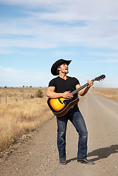 cowboy singing and playing the guitar on a dirt road