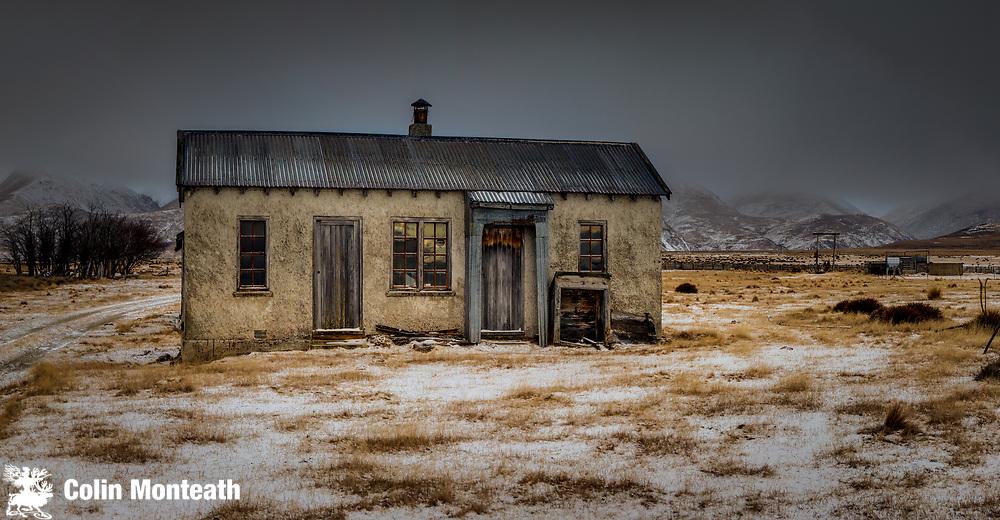 Historic farm cottage after winter snowfall, near St Bathans, Central Otago