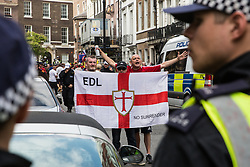 London, UK. 10th June, 2018. Supporters of the English hold a flag as they protest against the pro-Palestinian Al Quds Day march through central London organised by the Islamic Human Rights Commission. An international event, it began in Iran in 1979. Quds is the Arabic name for Jerusalem.