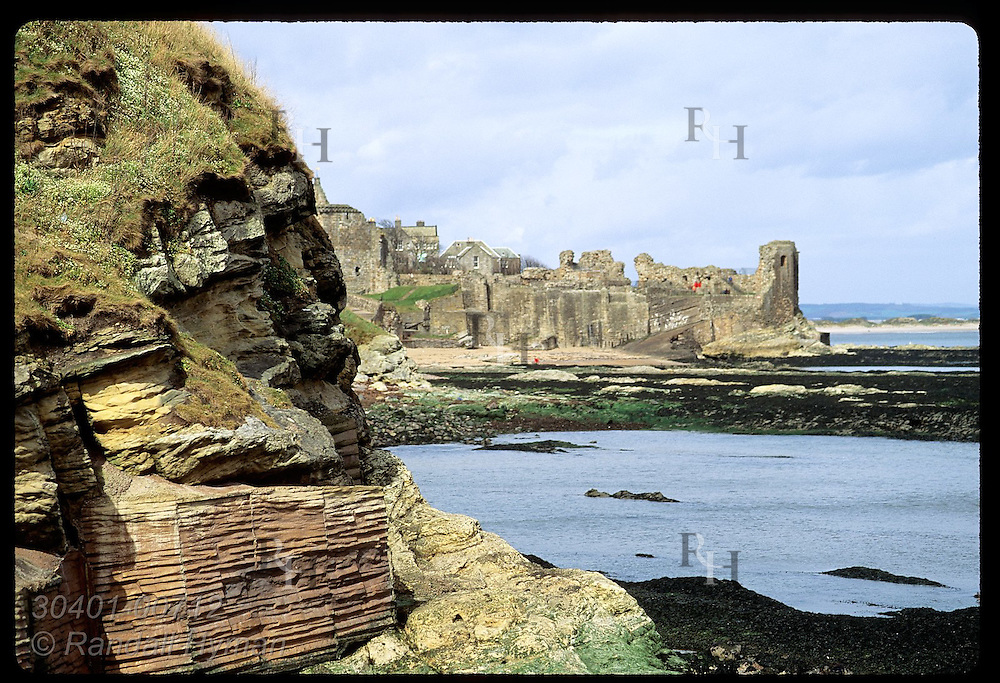 Ruins of St Andrews Castle sit on distant cliff overlooking calm seas on an April morn;St Andrews Scotland