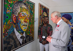 The Prince of Wales views an art work during a visit to the Jamestown Cafe in Accra, Ghana, on day four of his trip to west Africa with the Duchess of Cornwall.