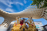 A float carrying a scene from the Passion of Christ, passes under the contemporary architecture of the Encarnation Market in Plaza de la Encarnacion in Seville. Andalusia, Spain