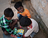 VARANASI, INDIA - CIRCA NOVEMBER 2018: Portrait of kids from a fishing village close to Varanasi playing on the street. Varanasi is the spiritual capital of India, the holiest of the seven sacred cities and with that many rituals and offerings are performed daily by priests and hindus.