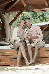 Romanic holiday couple sitting drinking cocktail