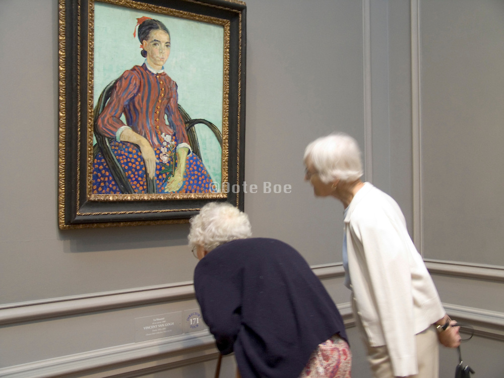 two elderly studying the title of a painting by van Gogh National Gallery of Art Washington DC USA