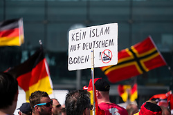 "Far-right demonstrators protest against Islam, refugees and Angela Merkel in Berlin. Sign says "" No Islam on German soil""."