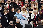 Melania Trump reaches out to her husband President-elect Donald Trump as he arrives for the 68th President Inaugural Ceremony on Capitol Hill January 20, 2017 in Washington, DC. Donald Trump became the 45th President of the United States in the ceremony.