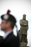 A man dressed in traditional Scottish outfit is framed by the state of Robert the Bruce before the start of Pipefest Stirling, an event staged at Stirling Castle to coincide with the 700th anniversary of the Battle of Bannockburn. The event was attended by 1600 pipers, Highland dancers and other musicians and formed a procession through the city's streets. The Battle of Bannockburn took place in 1314 and resulted in the defeat of Edward II's English army by the Scots under Bruce.