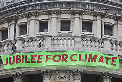 Activists from Africans Rising UK drop a banner from St Paul's Cathedral on the anniversary of the assassination of the Pan-Africanist President of Burkina Faso Thomas Sankara to launch the Jubilee for Climate Campaign on 15th October 2021 in London, United Kingdom. The Jubilee for Climate Campaign is an umbrella campaign both for the cancellation of debts for which Sankara fought so hard as well as for progressive and unifying policies to tackle the climate crisis which amplify voices from the Global South.