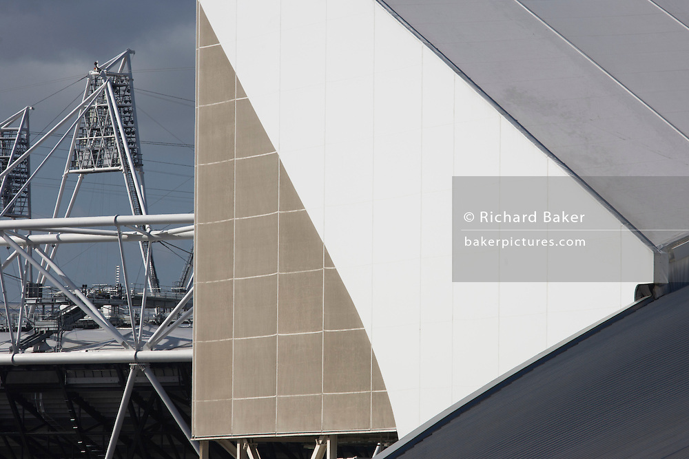2012 Olympic landscape showing Aquatics centre by Pritzker prize winner Zaha Hadid and main stadium at Stratford. The London Aquatics Centre has 2 50m swimming pools and a 25m diving pool. Built by Balfour Beatty for £242, three times the original cost. The aluminium roof is provided by Kalzip with cooperation from Rowecord Engineering and is 1,040 sq metre, weighing 3,200 tonnes.