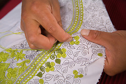 South America, Ecuador, Zuleta, hands embroidering tablecloth (close-up)