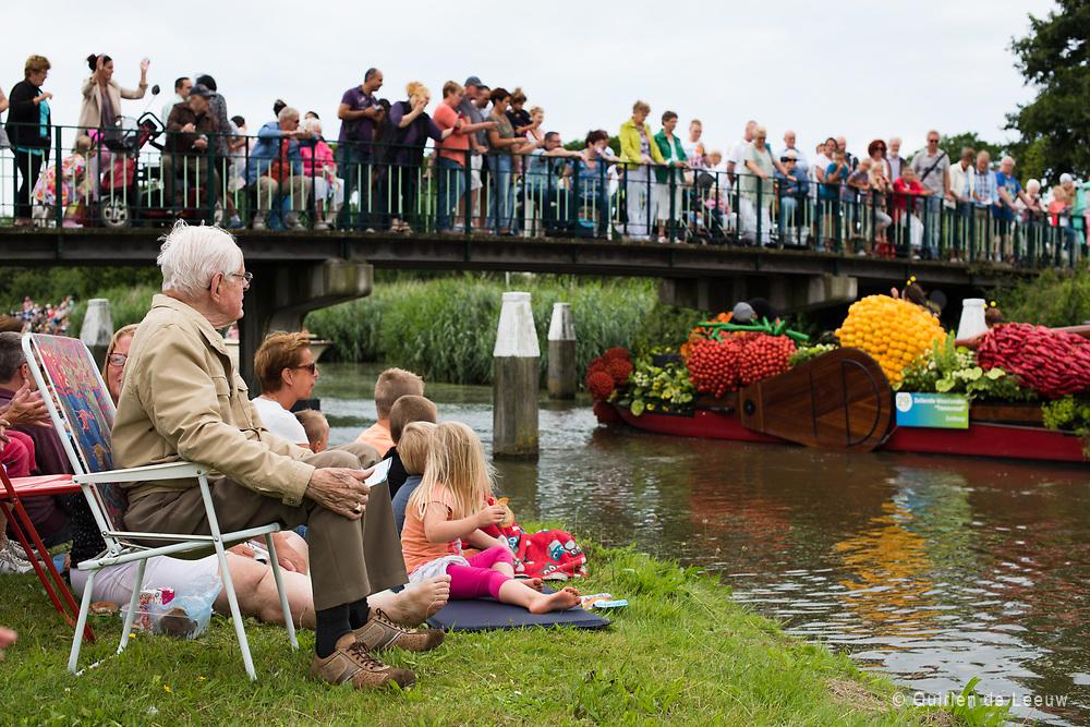 Bezoekers kijken naar het varende Bloemencorso, Westland.