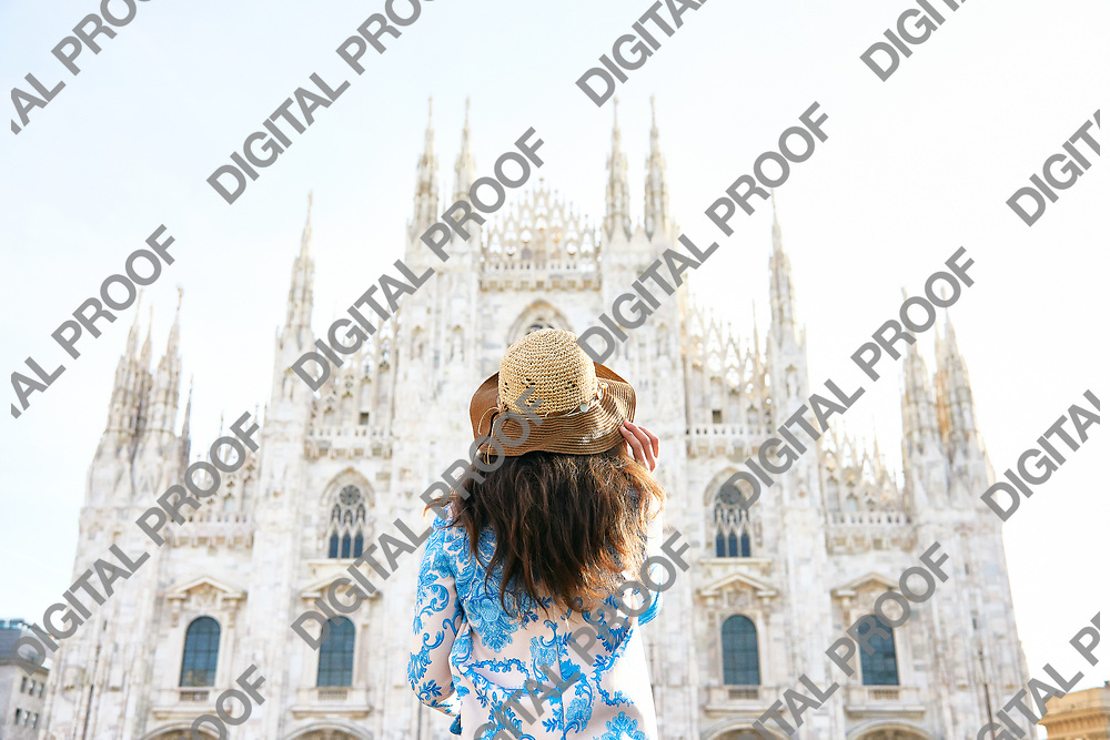 Travelver with a hat looking the front of Milan Duomo in Italy during the day