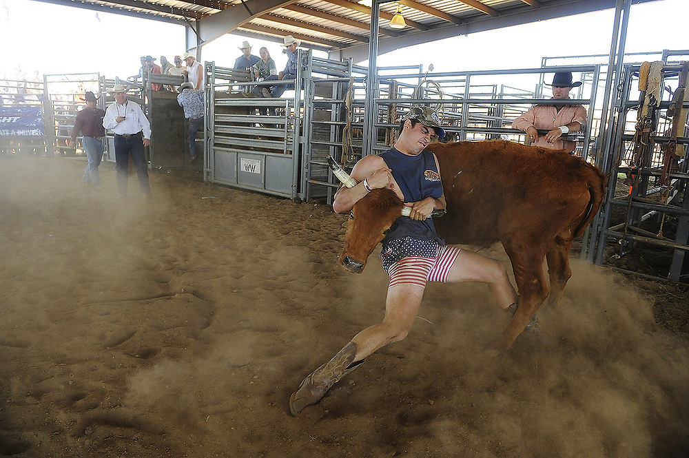 A participant braces himself for a throw during the steer wrestling event at the Alpha Psi Rodeo in Auburn, Ala. on Saturday, April 12, 2014.<br /> Zach Bland