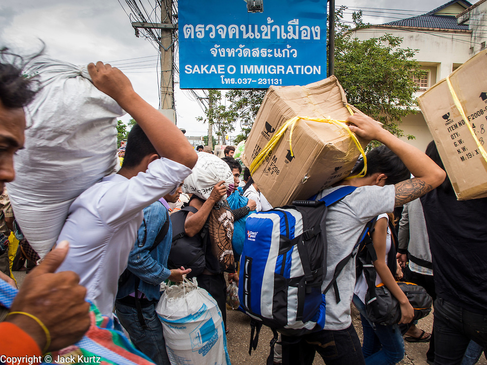 16 JUNE 2014 - ARANYAPRATHET, THAILAND: Cambodian migrant workers fleeing Thailand walk into the immigration police station in Aranyaprathet, Thailand before being returned to Cambodia. More than 150,000 Cambodian migrant workers and their families have left Thailand since June 12. The exodus started when rumors circulated in the Cambodian migrant community that the Thai junta was going to crack down on undocumented workers. About 40,000 Cambodians were expected to return to Cambodia today. The mass exodus has stressed resources on both sides of the Thai/Cambodian border. The Cambodian town of Poipet has been over run with returning migrants. On the Thai side, in Aranyaprathet, the bus and train station has been flooded with Cambodians taking all of their possessions back to Cambodia. PHOTO BY JACK KURTZ