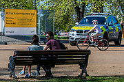 One couple ignore the signs and the remnants of tape and enjoy a chat on one of the benches, right in front of an armed response police car - Clapham Common is fairly busy as the sun is out but Lambeth Council has taped up all the benches, put up signs and organised patrols by wardens. The 'lockdown' continues for the Coronavirus (Covid 19) outbreak in London.