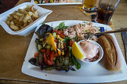 Delicious seafood lunch, crab salad, at Wainwrights Bar at the Bay Hotel, Robin Hood's Bay, North York Moors National Park, North Yorkshire county, England, UK, Europe. On our England Coast to Coast hike day 13 of 14, we went from Grosmont to Robin Hood's Bay on foot and via van.  We walked a rural path through bracken, purple blooming heather moors, and farmland before descending cliffs to the beach and village of Robin Hood's Bay. We dipped our boots into the North Sea, having completed our journey via foot and car from the Irish Sea over two weeks. [This image, commissioned by Wilderness Travel, is not available to any other agency providing group travel in the UK, but may otherwise be licensable from Tom Dempsey – please inquire at PhotoSeek.com.]