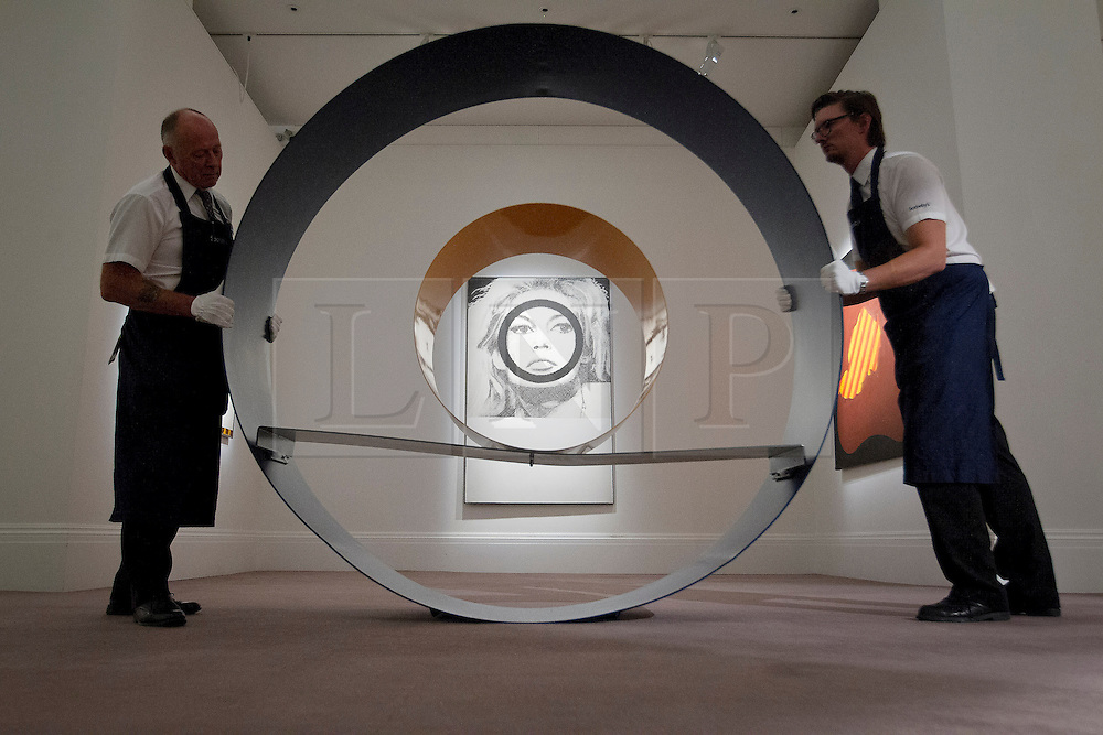 """© Licensed to London News Pictures. 03/09/2013. London, UK. Two Sotheby's employees adjust David Annesley's """"Untitled (Circle)"""" (1966) with Gerald Laing's """"Bridget Bardot"""" (1963) in the background during the press view for an exhibition of art from the 1960's at Sotheby's in London today (03/09/2013). The exhibition, entitled """"The New Situation: Art in London in the Sixties"""" and located at the auction house's New Bond Street building, is open to the public from 4th to the 11th of September 2013. Photo credit: Matt Cetti-Roberts/LNP"""