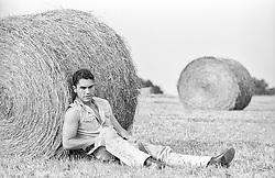 latin man relaxing against a large bale of hay