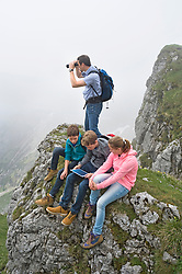 Father teenage kids using iPad in mountains