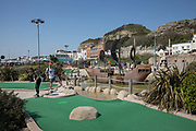 A couple play miniature golf on the 20th April 2019 in Hastings in the United Kingdom. Hastings is a town on England's southeast coast, its known for the 1066 Battle of Hastings.