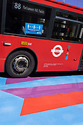 A Covid pandemic social distance sign is on the side of an 88 London bus as it passes over the multi-coloured markings of a crossing at Lower Regent Street, on 16th July 2021, in London, England. Days before the UK governments widespread re-opening of Covid pandamic restrictions Monday 19th July aka Freedom Day, the number of daily infections has risen to 50,000.