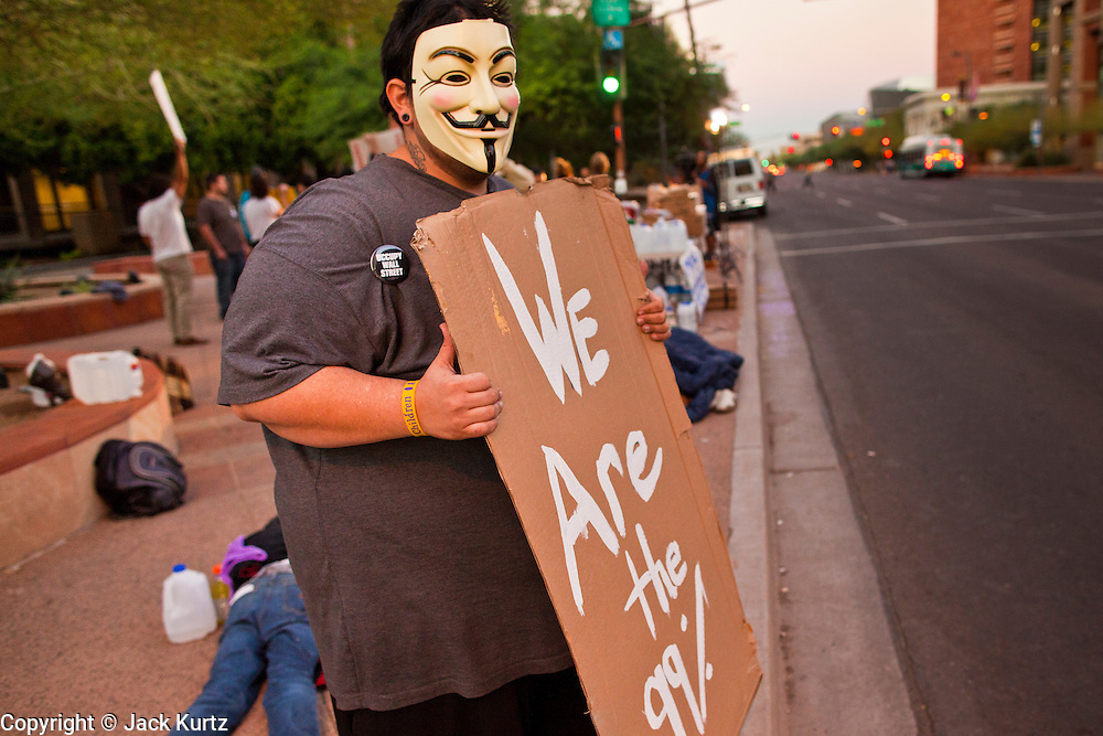 17 OCTOBER 2011 - PHOENIX, AZ:   An Occupy Phoenix protester pickets in front of Cesar Chavez Plaza in Phoenix, Monday. About 40 people spent Sunday night on the sidewalks around the Cesar Chavez Plaza in Phoenix, AZ, the defacto headquarters of the Occupy Phoenix protest. Early Monday morning they got up to continue their chants and protests against Wall Street, the growing income gap between rich and poor in the US, and money in politics. Monday marks the third day of Occupy Phoenix.    PHOTO BY JACK KURTZ