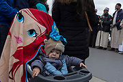 A child with a cartoon towel face sits in its buggy on Westminster Bridge, on 29th March 2017, in London, England.