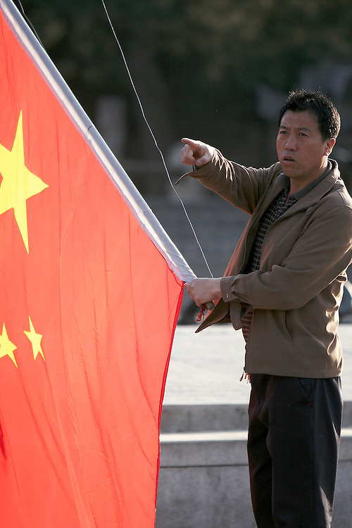 A worker from the Badaling section of The Great Wall raises the flag of the People's Republic of China at 6am before the gates open.