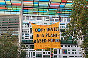 """The banner hanging on the Home Office building entry reads """"COP26: Invest in a Plant-based future"""". It is unveiled by Animal Rebellion protestors who have scaled DEFRA in the early morning of Tuesday, Oct 26, 2021, in central London, demanding government support for a plant-based food system ahead of COP26 which is to be held in six days. The protestors have said that they will take action until the government defunds meat and subsidises a plant-based transition. (VX Photo/ Vudi Xhymshiti)"""