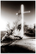A Cross Sits On A Bluff Overlooking The Ocean