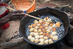"""30 May 2019, Mokolo, Cameroon: Today is market day, and refugees and host communities alike gather to sell and buy goods in Minawao. Here, Falta Mustafa makes """"Kosi"""", or 'bean cake' which she sells at the market. The Minawao camp for Nigerian refugees, located in the Far North region of Cameroon, hosts some 58,000 refugees from North East Nigeria. The refugees are supported by the Lutheran World Federation, together with a range of partners."""