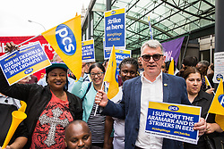 London, UK. 15 July, 2019. Mick Cash, General Secretary of the RMT trade union, poses with catering and cleaning staff belonging to the PCS trade union and outsourced to work at the Department for Business, Energy and Industrial Strategy (BEIS) via contractors ISS World and Aramark on the picket line outside the Government department after walking out on an indefinite strike for the London Living Wage, terms and conditions comparable to the civil servants they work alongside and an end to outsourcing.
