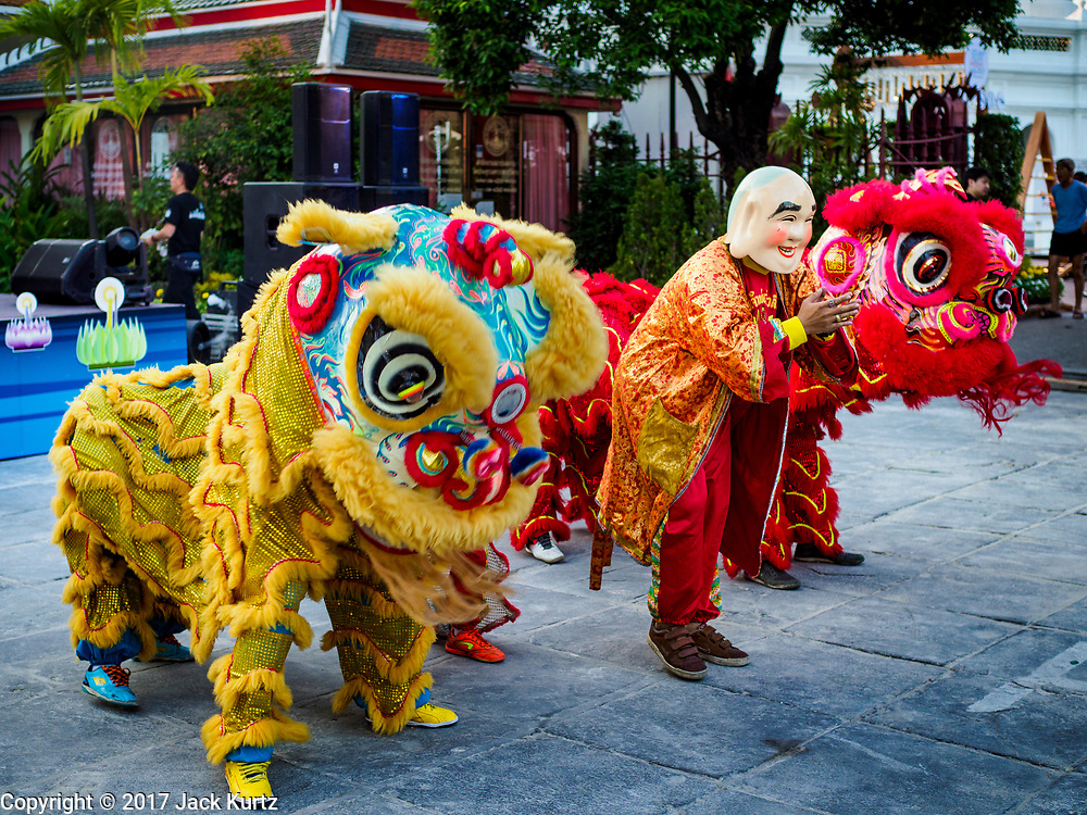 """03 NOVEMBER 2017 - BANGKOK, THAILAND:  Chinese style lion dancers perform during Loi Krathong at Wat Prayurawongsawat on the Thonburi side of the Chao Phraya River. Loi Krathong is translated as """"to float (Loi) a basket (Krathong)"""", and comes from the tradition of making krathong or buoyant, decorated baskets, which are then floated on a river to make merit. On the night of the full moon of the 12th lunar month (usually November), Thais launch their krathong on a river, canal or a pond, making a wish as they do so. Loi Krathong is also celebrated in other Theravada Buddhist countries like Myanmar, where it is called the Tazaungdaing Festival, and Cambodia, where it is called Bon Om Tuk.    PHOTO BY JACK KURTZ"""