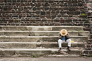 A man wearing a straw hat sits on stone steps of a small temple, his face in his hands, in the archeological site of Teotihuacan, Mexico state, Mexico.