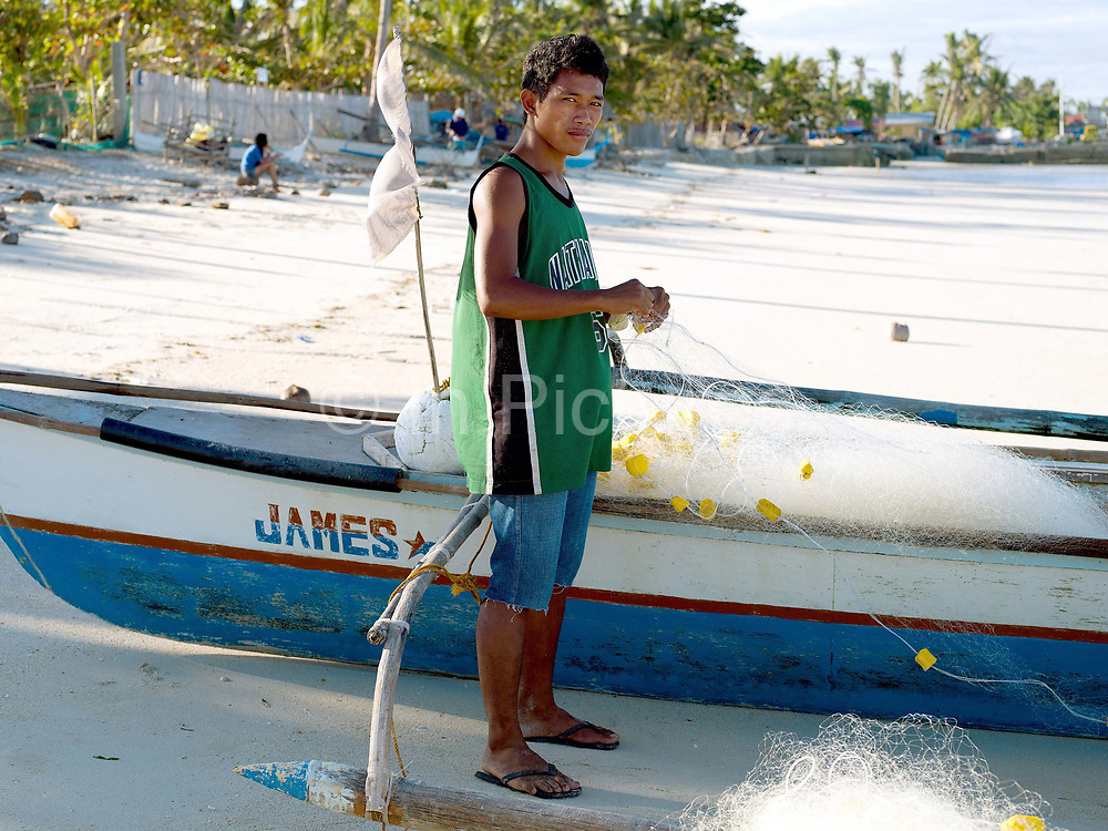 Fisherman Algun Villarosa (17) prepares his fishing nets before going fishing, Talisay, Santa Fe, Bantayan Island, The Philippines. On November 6 2013 Typhoon Haiyan hit the Philippines and was one of the most powerful storms to ever make landfall. The storm had a devastating impact on the fishing and seaweed industry and caused extensive environmental damage which will have a long term impact on ecosystems and the communities who rely on them for food and employment. Three-quarters of the island's population of about 136,000 depend on fishing as their main source of income. Thousands lost their boats and equipment in the storm. Oxfam is working to support the immediate and long-term needs of affected communities on Bantayan Island including establishing boat repair stations in Bantayan.