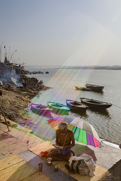 A holy man studying Hindu scriptures beneath a colourful umbrella, sitting on a ghat beside the river Ganges, Durga Ghat, Varanasi, India