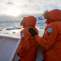 A couple on the bow of the National Geographic Explorer share the magic of the moment as they observe the stunning landscape after the ship exited the Lemaire Channel in Antarctica.