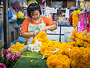 18 JULY 2013 - BANGKOK, THAILAND:  A woman makes flower garlands in the Onnuch (also known as On Nut) Wet Market off of Sukhumvit Soi 77 in Bangkok.       PHOTO BY JACK KURTZ