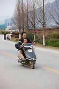 Man and child on a scooter near Guilin, China. China has a one child family planning policy to reduce population.