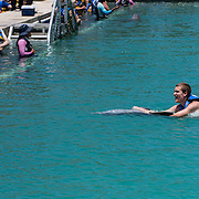 North America, Caribbean, Cayman Islands, Cayman, Grand Cayman, Georgetown, <br /> Visitors have an opportunity to swim with a trained dolphin in Grand Cayman.