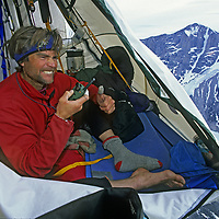 BAFFIN ISLAND, NUNAVUT, CANADA. Mountaineer Alex Lowe, in hanging camp, hears on radio that leaders are near summit of Great Sail Peak. Stewart Valley bkg. (MR)