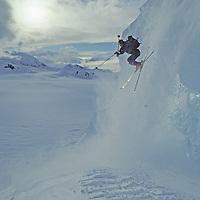 ANTARCTICA. Ski mountaineer Mike Farny (MR) jumps icy serac on Mount Berry above Calley Glacier, Danco Coast, Antarctic Peninsula.