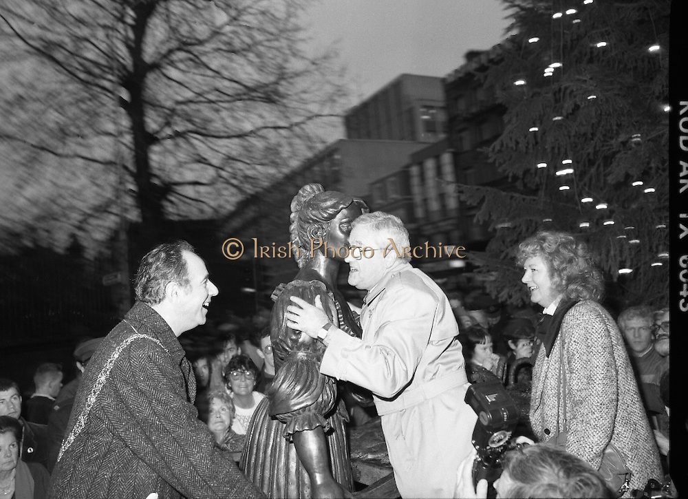 """Molly Malone Statue Unveiled. (R93)..1988..20.12.1988..12.20.1988..20th December 1988..""""Dublin's Fair City"""" received a millenniun gift to commemorate her most famous daughter, Molly Malone, when Jurys Hotel Group plc presented a specially commissioned sculpture to the people of Dublin. The sculpture was formally handed over by Michael McCarthy, MD,Jurys Hotel Group, to the Lord Mayor of Dublin, Councillor Ben Briscoe, TD, in an unveiling ceremony today at the corner of Grafton Street, Suffolk Street and Nassau Street..Molly Malone was created and fashioned in her traditional 17th century dress by Dublin born artist, Jeanne Rynhart, who was selected from a number of entries for the statue design, by the Dublin Millennium Board...Image shows Mr Michael McCarthy of Jurys Hotel Group coming to grips with Molly as artist Jeanne Rynhart and Lord Mayor Ben Briscoe look on."""