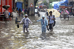 July 25, 2018 - Kolkata, West Bengal, India - School student wades through a water log street after monsoon rain. Spells of rain and thundershower occurred in Kolkata and others part of West Bengal. (Credit Image: © Saikat Paul/Pacific Press via ZUMA Wire)