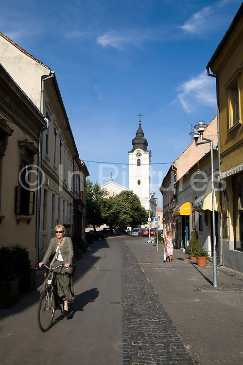 A woman rides a bicycle along the pretty shopping street of Ferencesek Utcaja (street).Pecs has been chosen as the 2010 European City of Culture. The city is on the southern slopes of the Mecsek Hills and has a sub-Mediterranean climate. Settled by Romans as Sopianae, it was a significant Christian settlement. Later conquered by the Ottomans, it has important Turkish architecture.