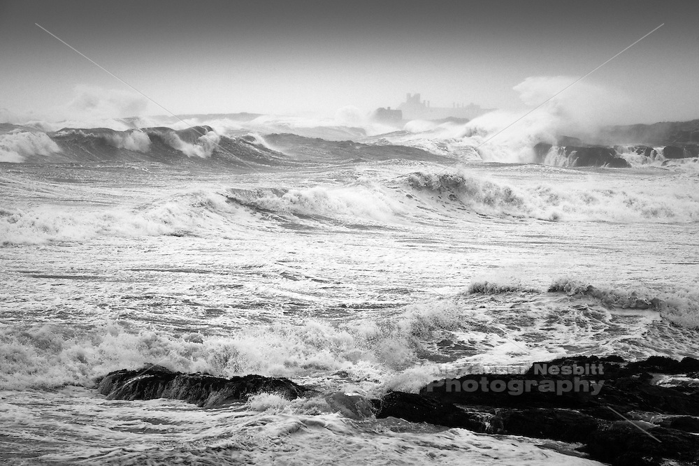 Newport, RI - huge waves from Hurricane Irene roll into Bailey's beach.  In the distance the great houses on the ocean drive appear dwarfed and lost in the spray and mist.